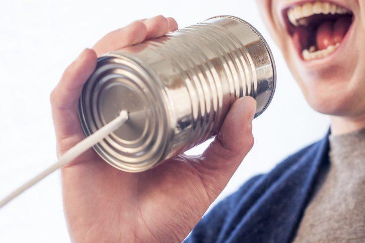 Man communicating via tin can